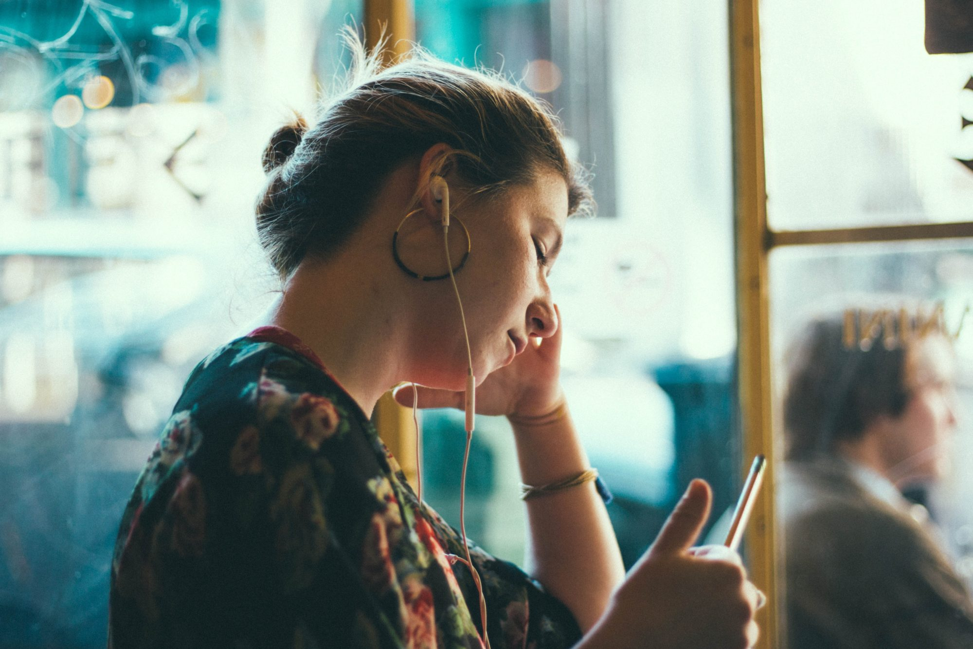 a woman sits in a cafe with her headphones in. she is looking at her phone and looking calm.