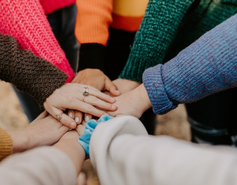 A photograph of many hands in the center together, collected one on top of each other.